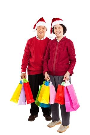 A shot of senior Asian couple carrying shopping bags celebrating Christmas
