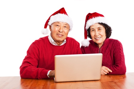 A shot of senior Asian grandparents using computer photo