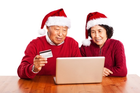 A shot of senior Asian couple shopping online celebrating Christmas photo
