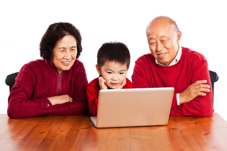 A shot of senior Asian grandparents using computer with their grandson Banco de Imagens