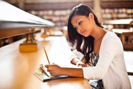 college campus: A shot of an Asian student studying in the library