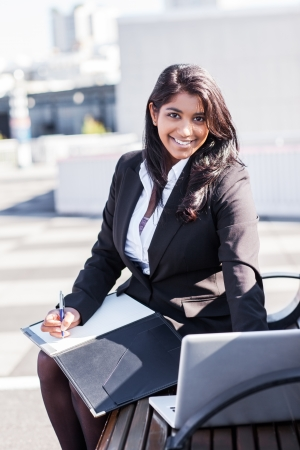 A shot of an Indian businesswoman working on her laptop outdoor photo