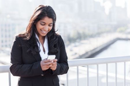 phone business: A shot of an Indian businesswoman texting on the phone  outdoor