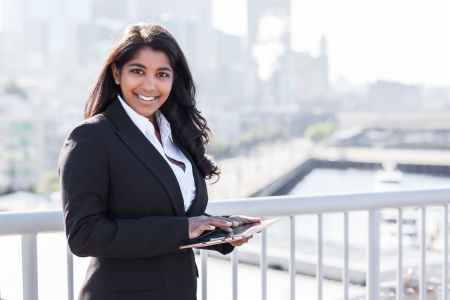 indian professional: A shot of an Indian businesswoman holding a tablet PC outdoor