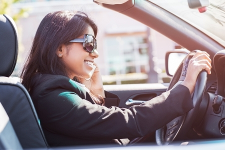 woman driving car: A shot of an Indian businesswoman driving a car and talking on the phone
