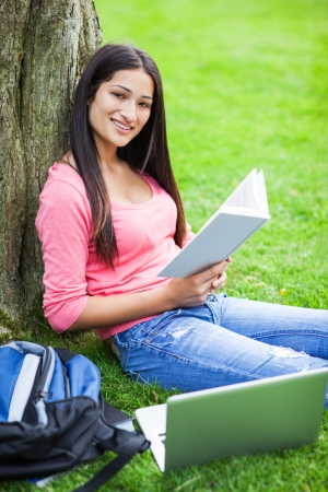 A shot of a hispanic college student sitting on the grass studying Banque d'images