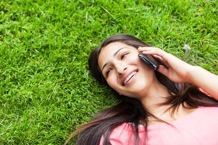 woman lying down: A shot of a hispanic student talking on the phone