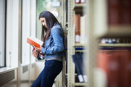A portrait of an Hispanic college student studying in the library Foto de archivo