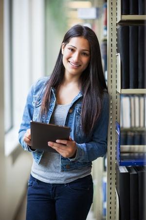 히스패닉 대학 학생의 초상화 태블릿 PC를 사용하여 라이브러리에서 공부 스톡 콘텐츠