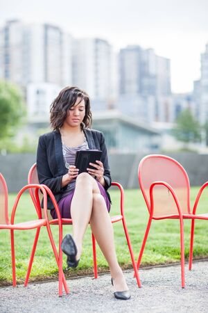 A shot of an African American businesswoman reading on her tablet PC at an outdoor park