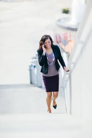 A shot of a happy African American businesswoman talking on the phone walking up the stairs