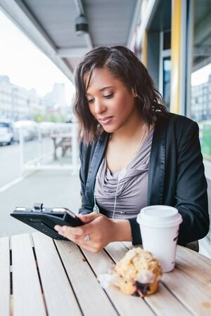 A shot of an African American businesswoman reading on her tablet PC at an outdoor cafe