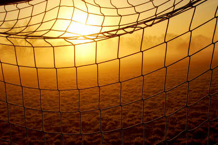 A detail of a net of a soccer goal with the sun and some fog in the background Stock Photo