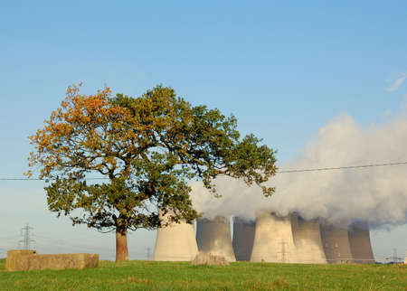 carbondioxide: Lonely tree in fornt of cooling towers of a power plant in England  Stock Photo