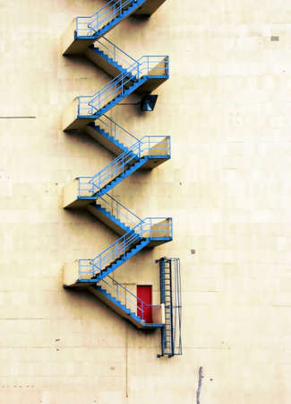 A blue fire escape staircase witht a red door on a white wall photo