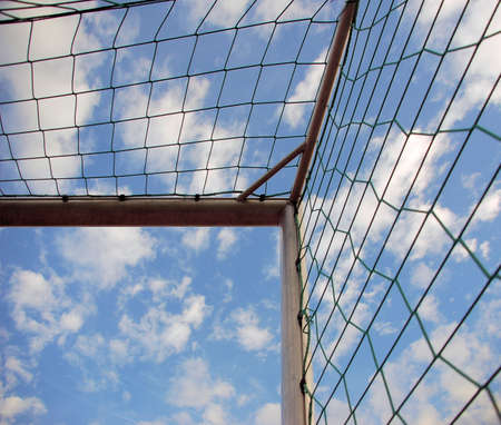 Soccer goal corner with net and blue sky with clouds photo