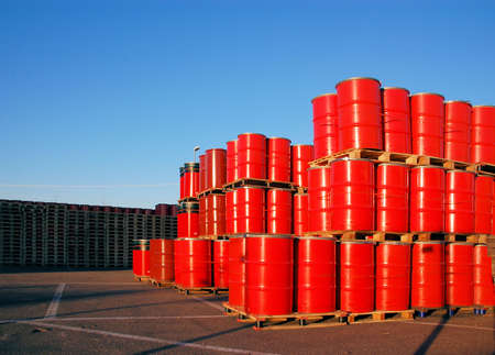Stack of red oil drums and wooden palettes
