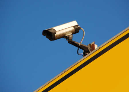 Security camera mounted on a yellow shield with a blue sky background Stock Photo - 2507445