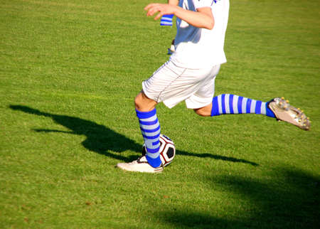 Soccer player shppting the ball on a green grass field Stock Photo - 3020624