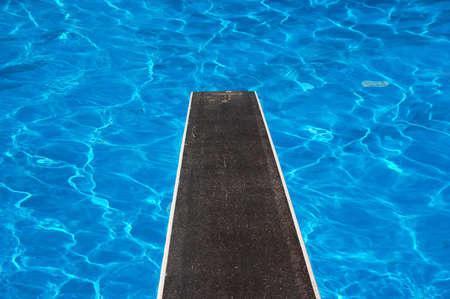 springplank: Zwembad met duikplank en reflecties Stockfoto