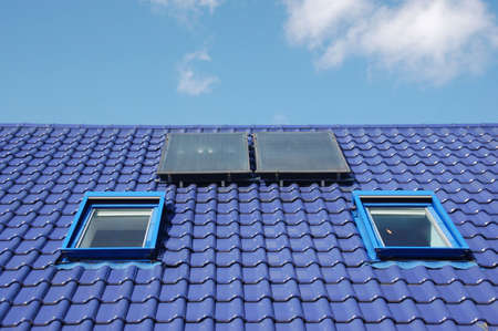 Blue tiles on a roof with window and solar energy recovery