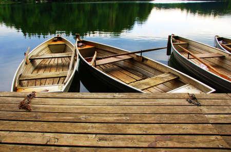Oude houten roeiboten op een houten pier Stockfoto