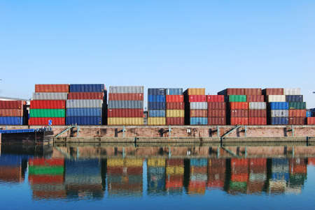 freight: Cargo container in a harbour with water reflections Stock Photo