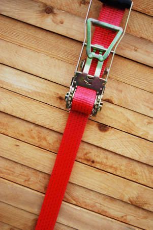 lashing: Red lashing strap on a pile of timber