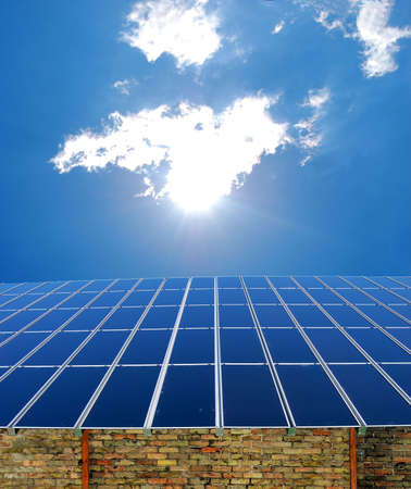 Solar panel on a roof with a bright sun and clouds Stock Photo - 4708989