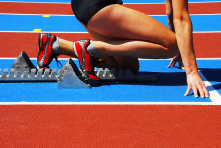 starting line: Woman in a starting block on an athletic field
