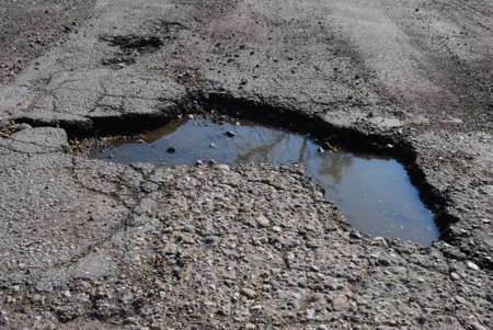 Pothole filled with water on a street Stock Photo