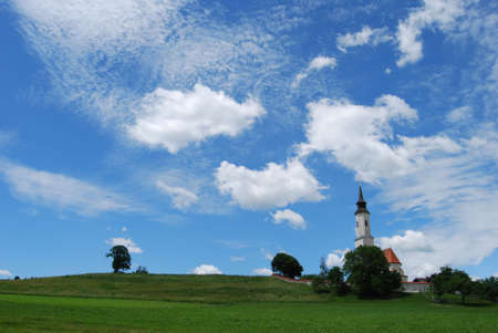 Church on top of a hill with a wild sky photo