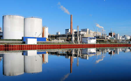 Industrial site with smoking stacks reflected in a river photo