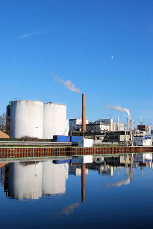 Chemical plant with reflection on a river photo