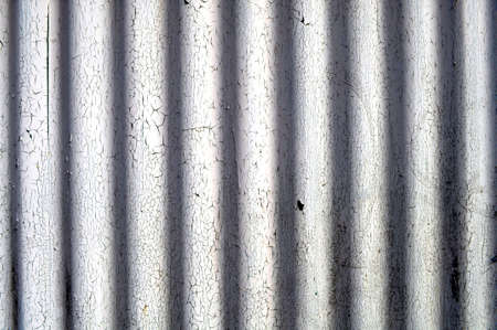 White corrugated metal plate with cracked paint photo