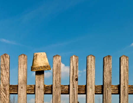 Vintage fence and a flower pot against a blue sky photo