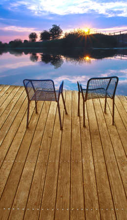 deck chair: Two empty chairs on a boardwalk during sundown on a lake