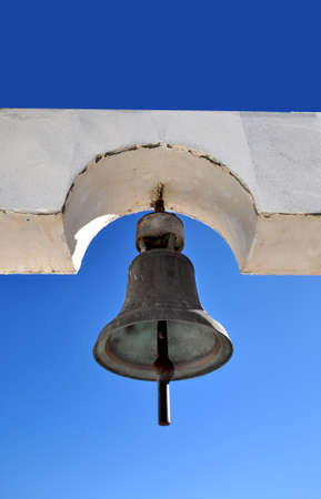 Old metal bell on a white church photo
