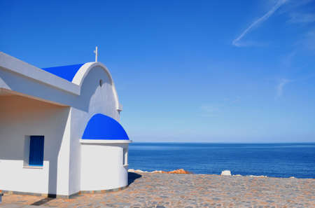 White chapel with blue roof on the beach in Cyprus