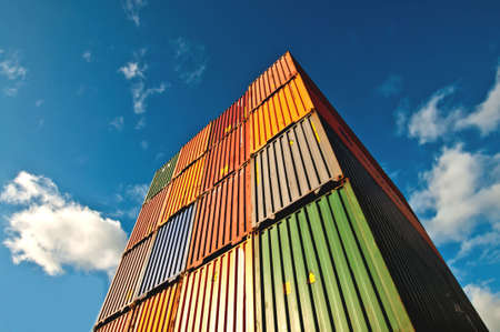 Upside view of a staple of cargo container against a blue sky with clouds
