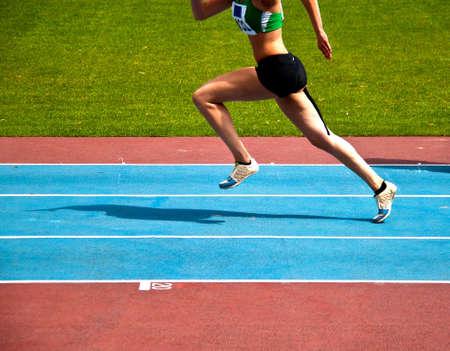 salto largo: Joven mujer de partida en una pista de athletioc para un triple salto Foto de archivo