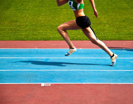 Young woman starting on an athletioc track for a triple jump