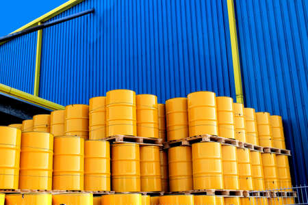 Yellow oil drums in front of a factory with blue cladding