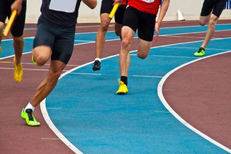 relay: Corredores en una pista de atletismo durante un relé Foto de archivo