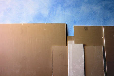sheetrock: Different sized gypsum plaster boards on a blue wall Stock Photo