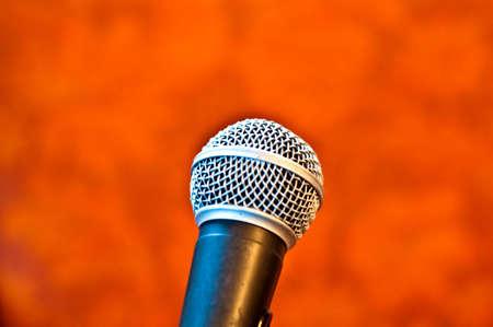 perform: Black microphone on an orange background