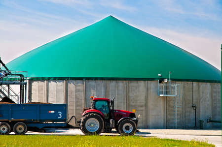 Red tractor in forn of a biogas plant Stock Photo