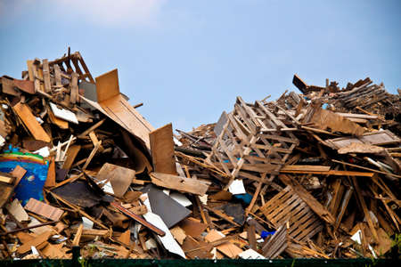 Wooden waste and a blue sky on a recycling plant Stock Photo