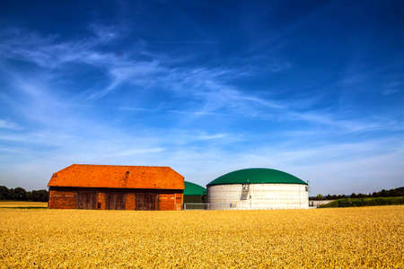 Biogas silo plant and a barn on a farm behind a field Stock Photo