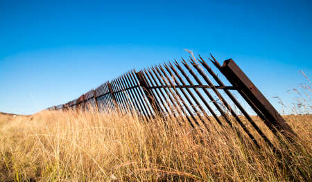 Metal fence and a grass landscape with blue sky 스톡 콘텐츠